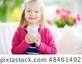 Cute little girl drinking fresh organic milk at sunny summer day. Healthy nutrition for children. 48461492