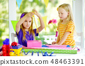 Two cute sisters wrapping gifts in colorful wrapping paper 48463391