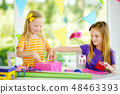 Two cute sisters wrapping gifts in colorful wrapping paper 48463393