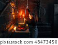 Scary witch cooking soup and reads spell 48473450