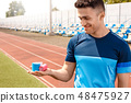 Young man on stadium outside standing with kinesio tape smiling cheerful close-up 48475927