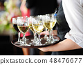 Waitress with a dish of champagne and wine glasses 48476677
