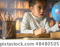 asian child industrious  is sitting at a desk   48480505