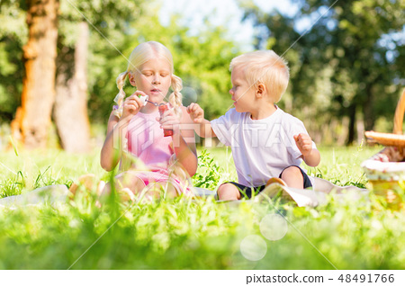 Pleasant children playing together in the park 48491766