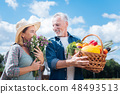 Blonde-haired wife feeling surprised and pleased after receiving field flowers 48493513