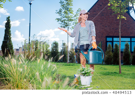 Woman caring about ecology and nature watering her garden bed 48494513