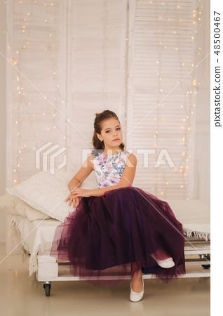 Beautiful girl in a purple dress and flower blouse posing for a photographer 48500467