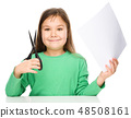 Little girl is cutting paper using scissors 48508161