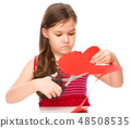 Portrait of a little girl cutting out red heart 48508535