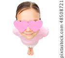 Little girl is holding hearts over her eyes 48508721
