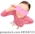 Little girl is holding hearts over her eyes 48508723