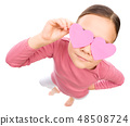 Little girl is holding hearts over her eyes 48508724