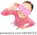 Little girl is holding hearts over her eyes 48508725