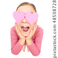 Little girl is holding hearts over her eyes 48508728