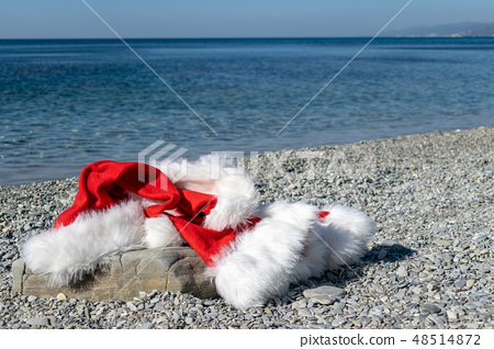 Santa Claus clothing and hat lies on a large stone 48514872