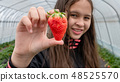 Asian American tween girl holding strawberry 48525570