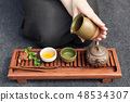 Traditional tea ceremony close up with woman hand 48534307