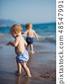 Two toddler children walking on a beach on summer holiday. 48547991