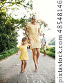 A young mother with small daughter playing hopscotch on a road in summer. 48548146