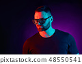 Portrait of a bearded serious man at studio. High Fashion male model in colorful bright neon lights 48550541