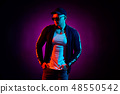 Portrait of a young happy serious man at studio. High Fashion male model in colorful bright neon 48550542
