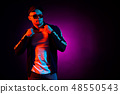 Portrait of a young happy serious man at studio. High Fashion male model in colorful bright neon 48550543