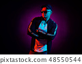 Portrait of a young happy serious man at studio. High Fashion male model in colorful bright neon 48550544