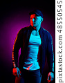 Portrait of a young happy serious man at studio. High Fashion male model in colorful bright neon 48550545
