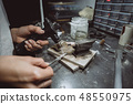 In the workshop, a woman jeweler is busy soldering jewelry 48550975