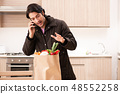 Young handsome man with vegetables in the kitchen  48552258