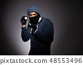 Young gangster in hood on grey background  48553496