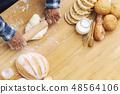 Man baking fresh bread on tray in garden 48564106