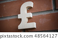 Wooden pound sterling symbol on a brick wall 48564127
