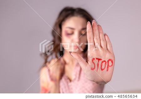 Domestic violence, protesting and people concept - brunette woman expressing denial with STOP on her 48565634