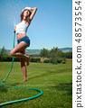 Beautiful young woman having fun in summer garden with garden ho 48573554