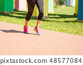 legs of girl running in a sports competition 48577084