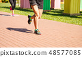 legs of two girls running in a sports competition 48577085