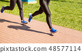 legs of two girls running in a sports competition 48577114