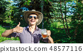 young man is drinking beer in the park 48577116