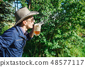 young man blowing foam from a beer in a mug 48577117