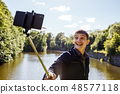 young man making selfie with a selfie stick 48577118