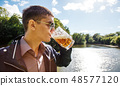 young man in sunglasses is drinking beer in the park 48577120