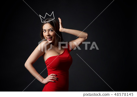Beautiful woman in red dress supporting her crown 48578145