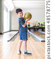 Cute child with ball in bowling club. 48578775
