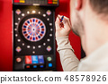 Man aiming against dartboard 48578926