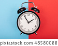 black metal arrow alarm clock on blue-red background 48580088