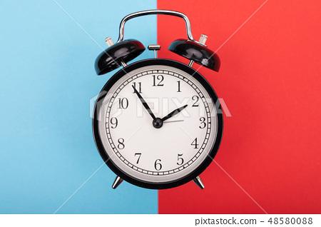 black metal arrow alarm clock on blue-red background 48580088