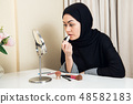 Portrait of beautiful muslim woman with hijab applying lipstick 48582183