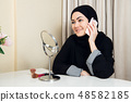 cheerful happy pretty muslim woman sitting and using mobile cell phone calling for friend chatting 48582185