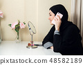 cheerful happy pretty muslim woman sitting and using mobile cell phone calling for friend chatting 48582189